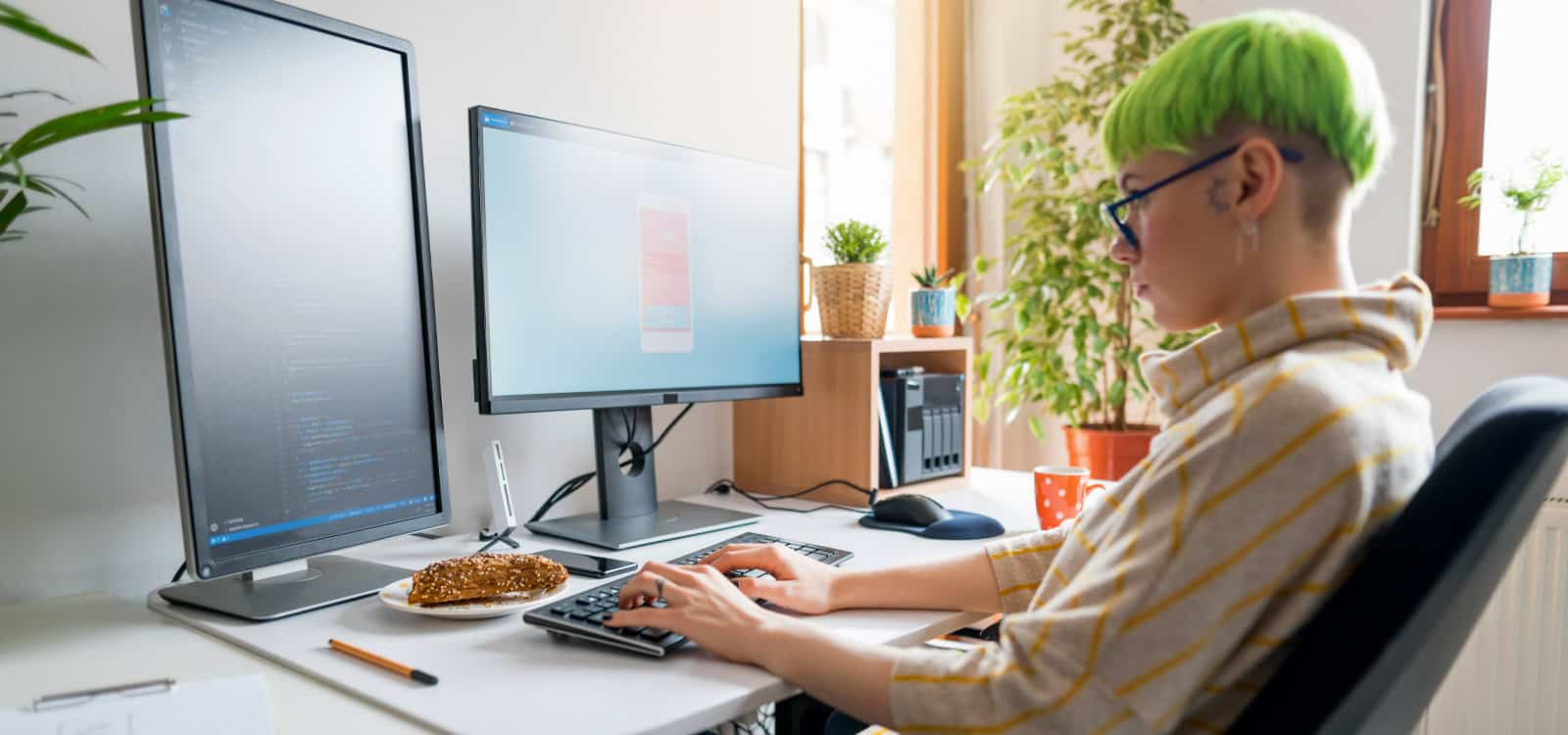 A person with green hair sits in front of dual monitors and appears to be coding, indicating she pursued the business idea of becoming an app developer