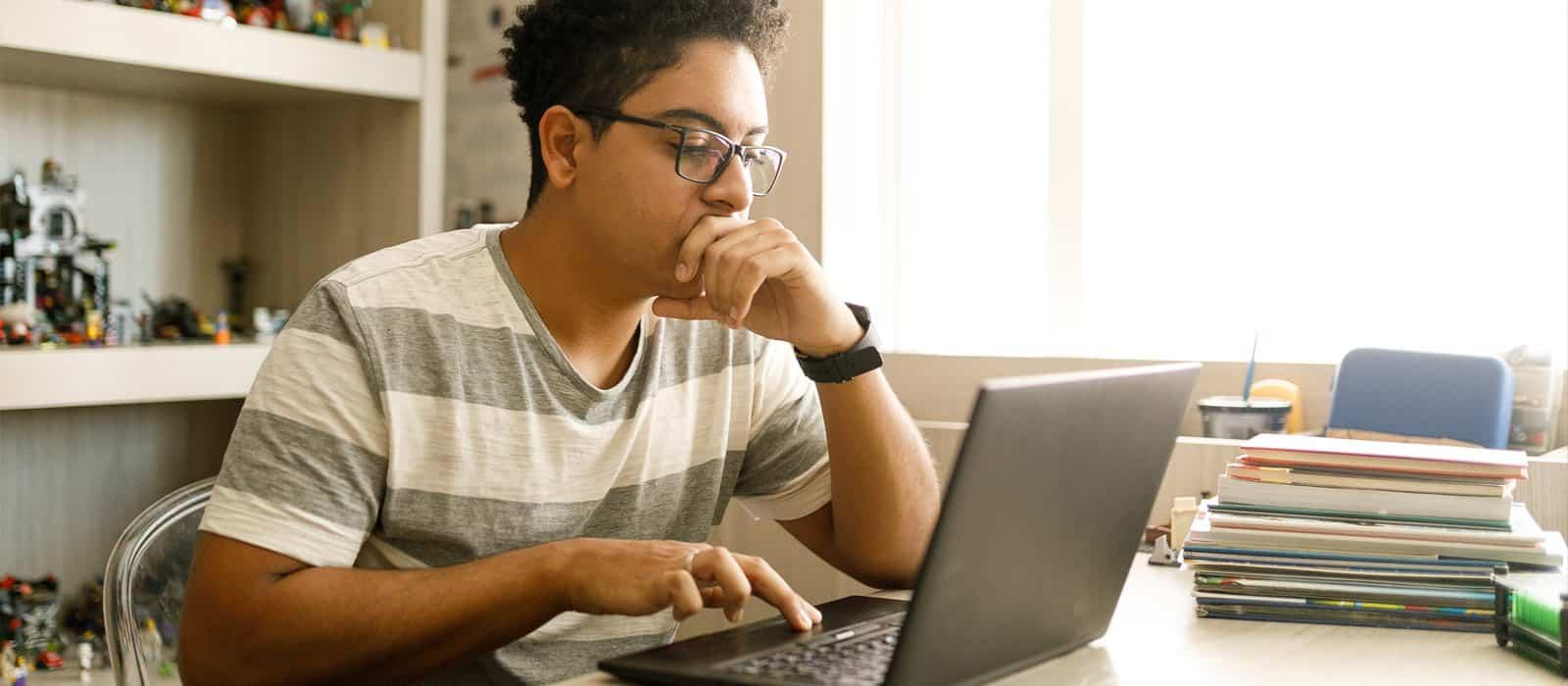 Male in striped shirt scrolling on black laptop