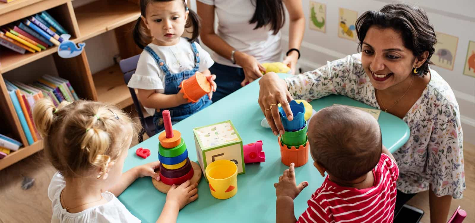 A woman is surrounded by children and plays with toys with them, indicating she pursued the business idea of becoming a daycare owner