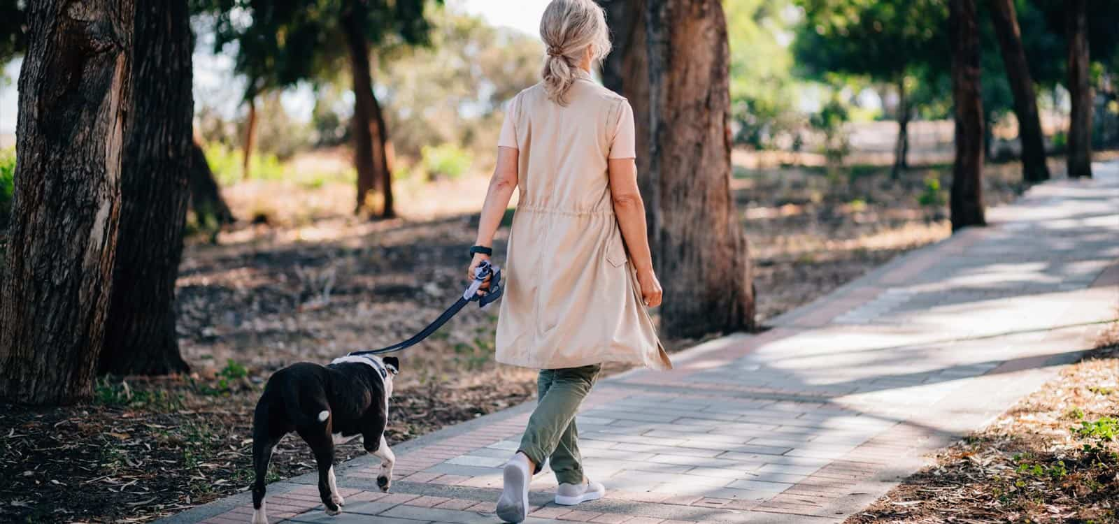 A blonde-haired woman in a trench walks a black dog in a park, indicating she pursued the business idea of becoming a dog handler