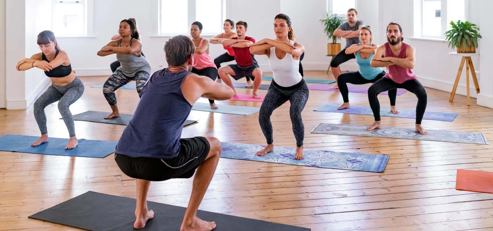 A man leads a group fitness class that's squatting in front of him, indicating he pursued the business idea of becoming a fitness instructor or trainer