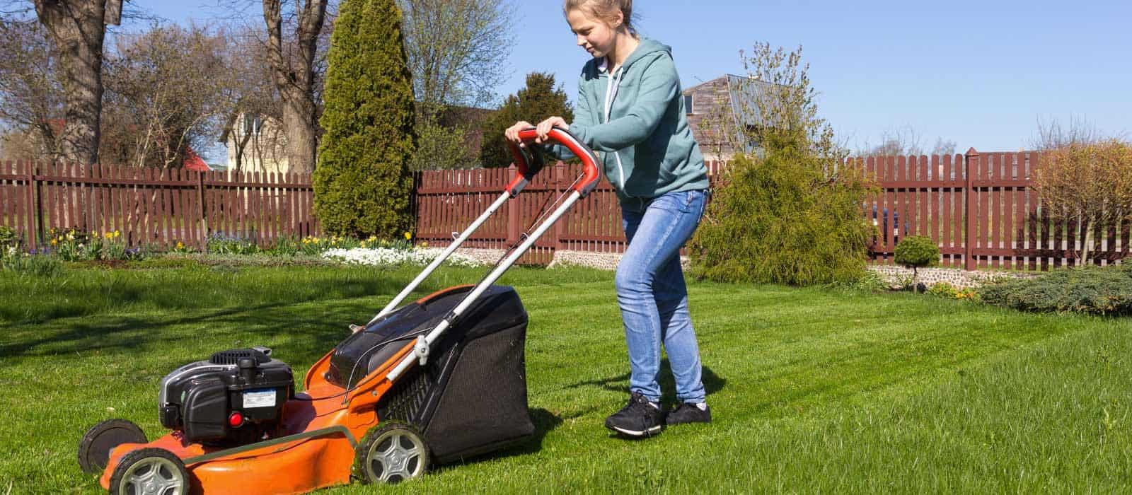 Female steering an orange lawnmower on a lawn in a backyard