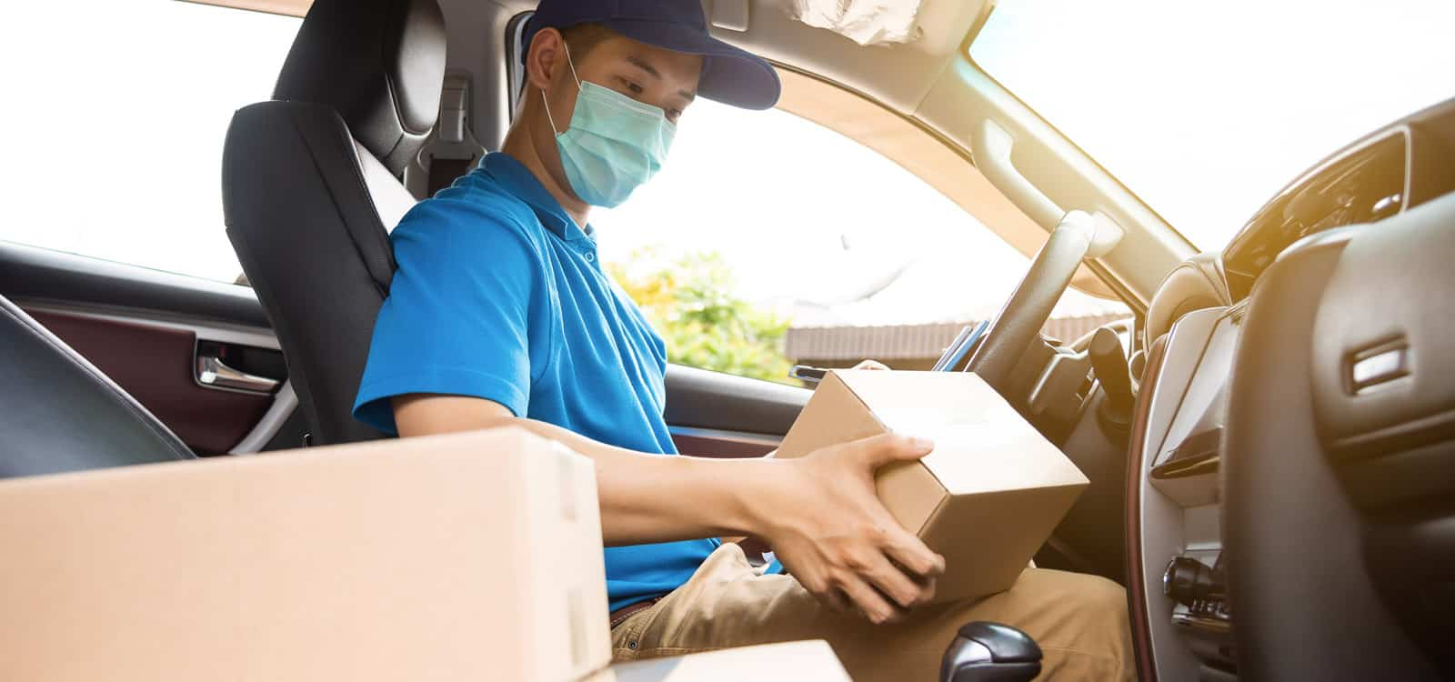 A person in a mask and black hat handles a box in a car, indicating they pursued the small business idea of becoming a medical courier