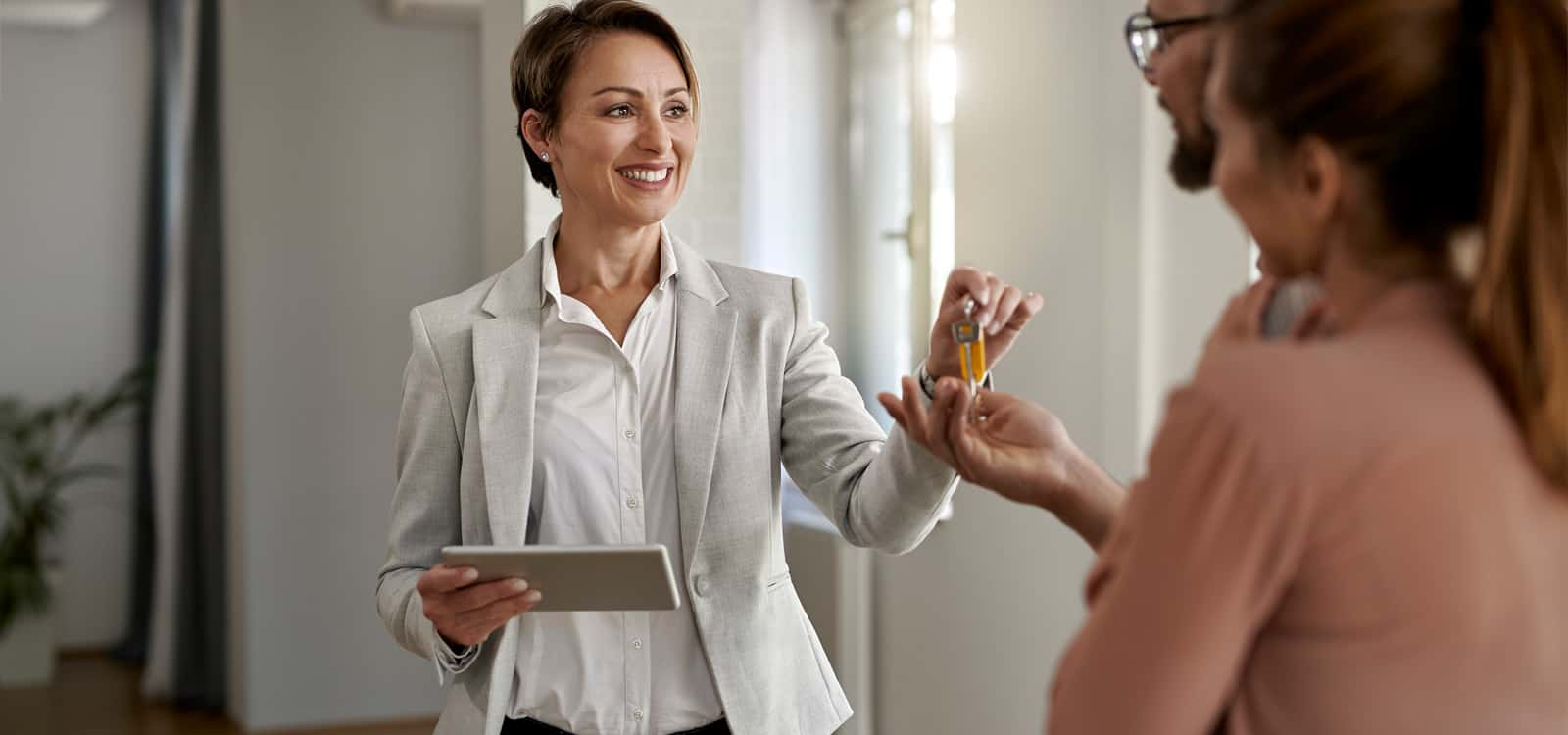 A woman in a blazer hands a pair of keys to couple, indicating she pursued the small business idea of becoming a real estate agent