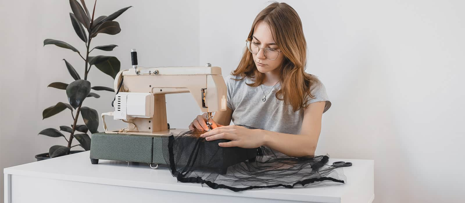 Female teen using sewing machine next to plant