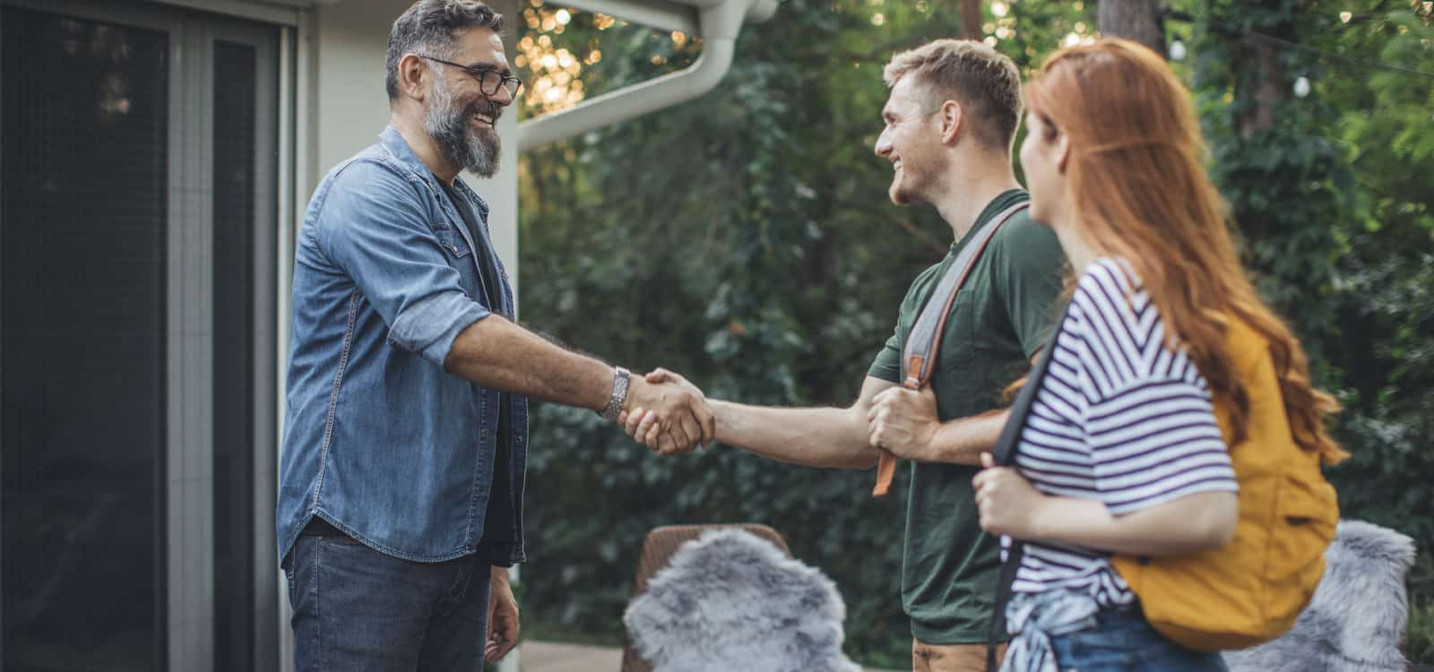 A bearded gentleman shakes the hand of a couple walking up to his home, indicating he pursued the small business idea of becoming a vacation rental host