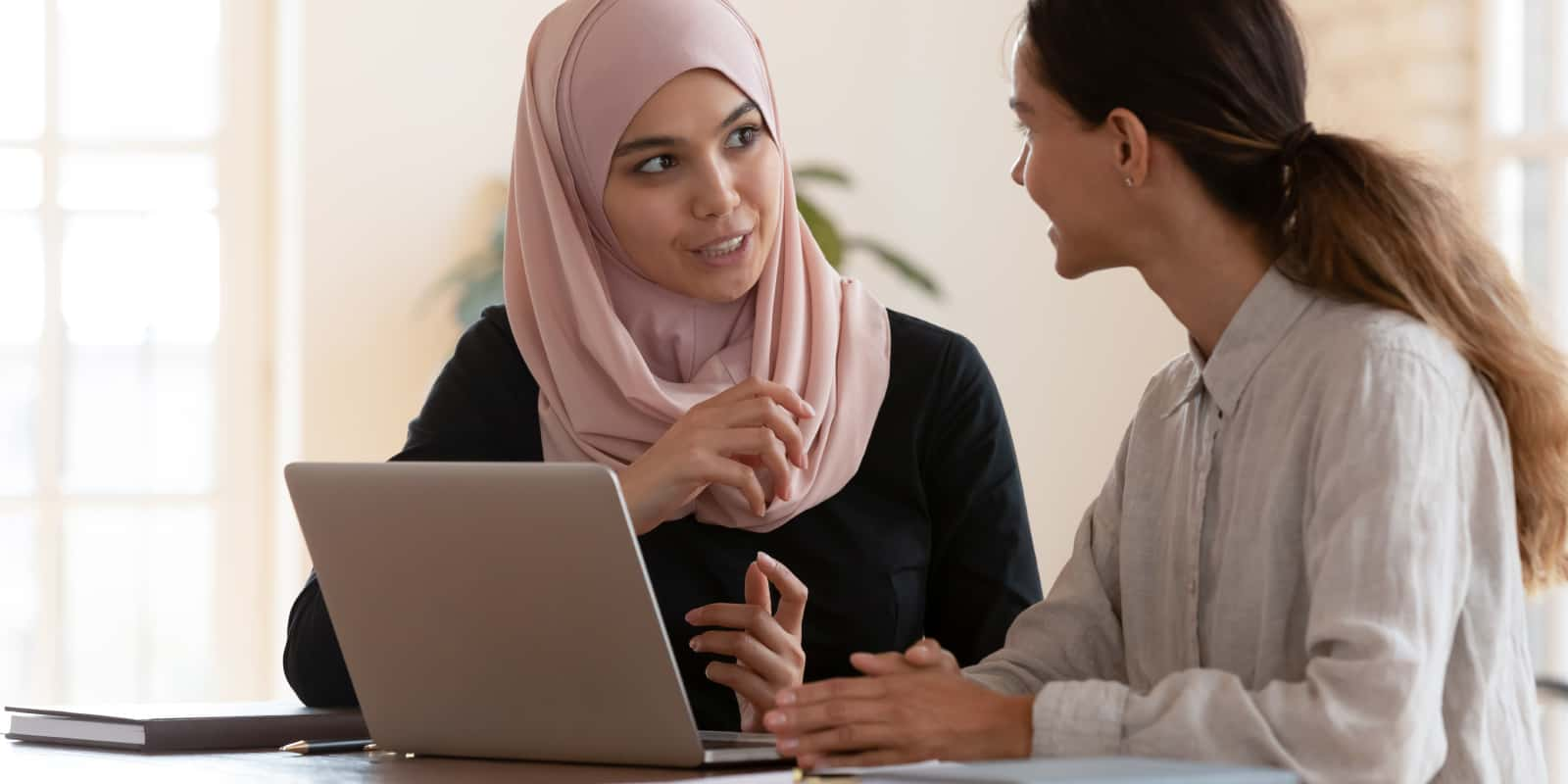 Two women talking with a laptop open in front of them