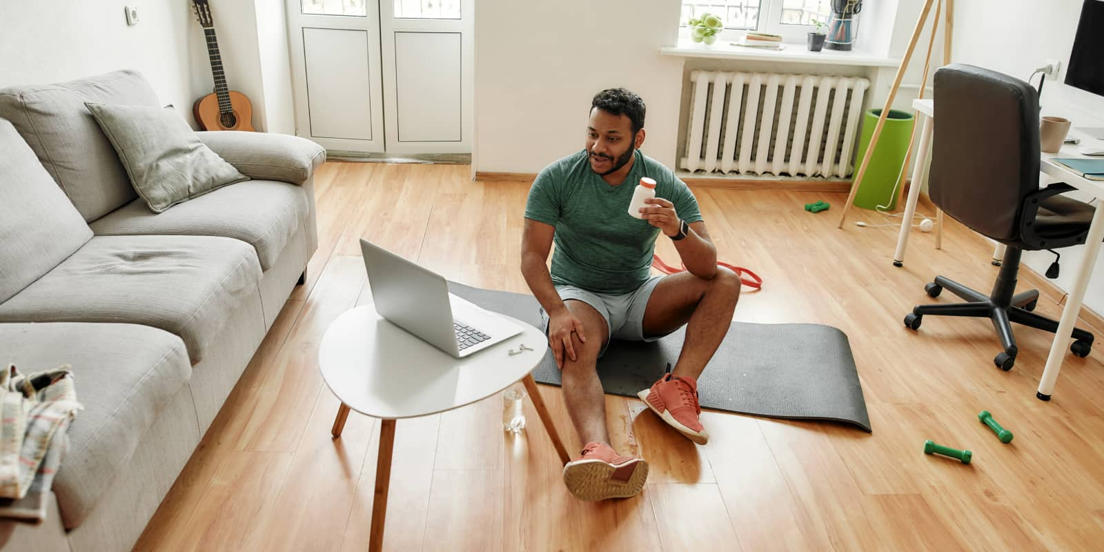Man on wood floor with yoga mat doing a workout over video call on laptop