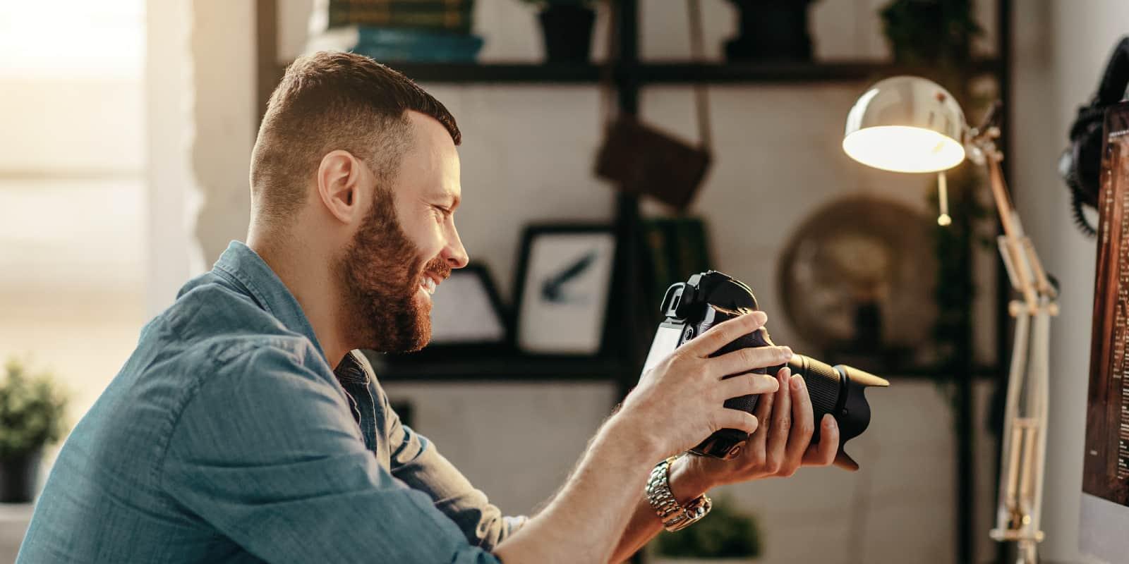 Man holding camera and smiling while looking at camera screen