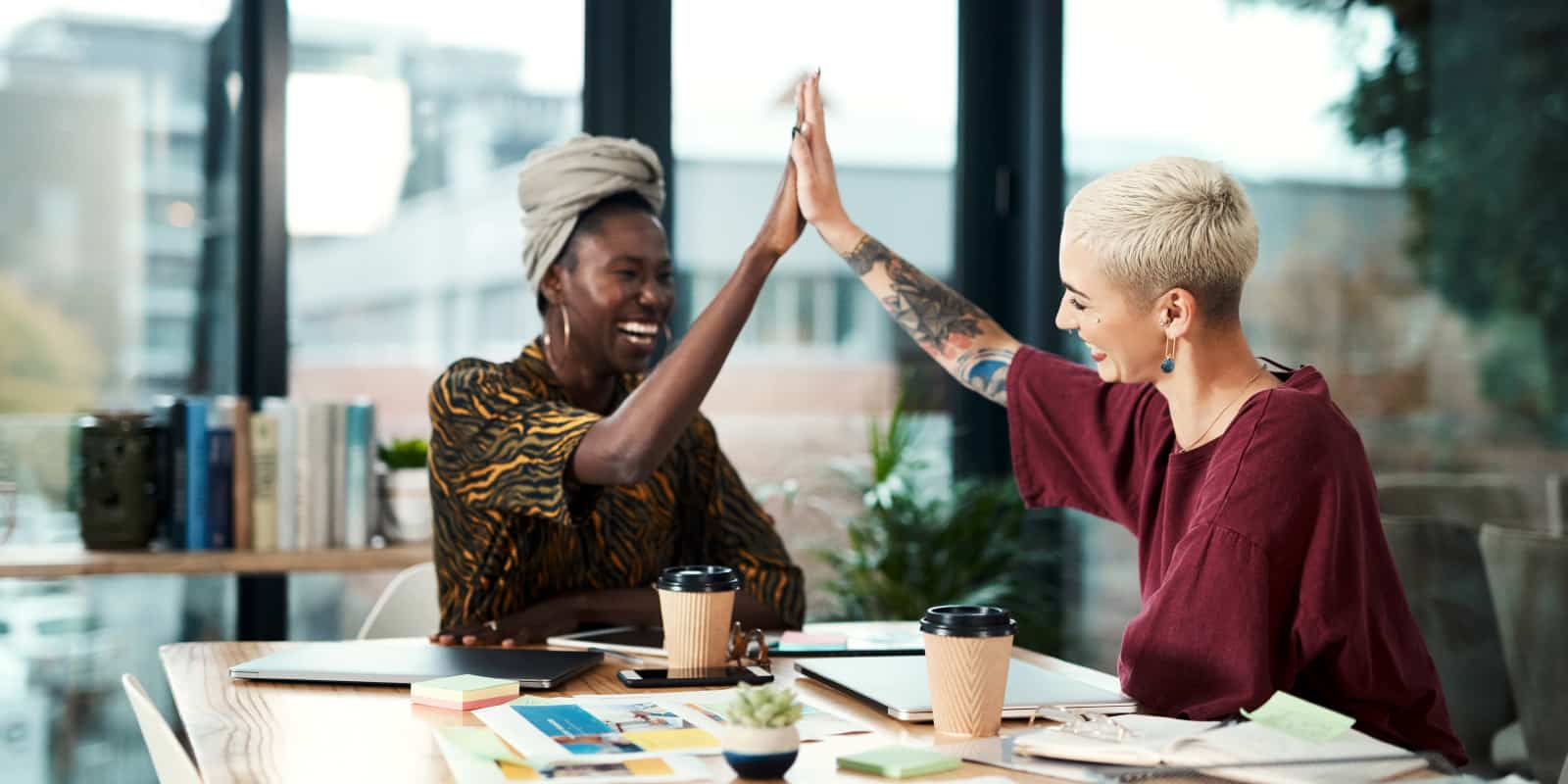 Two women high fiving next to coffee cups and paper on a table