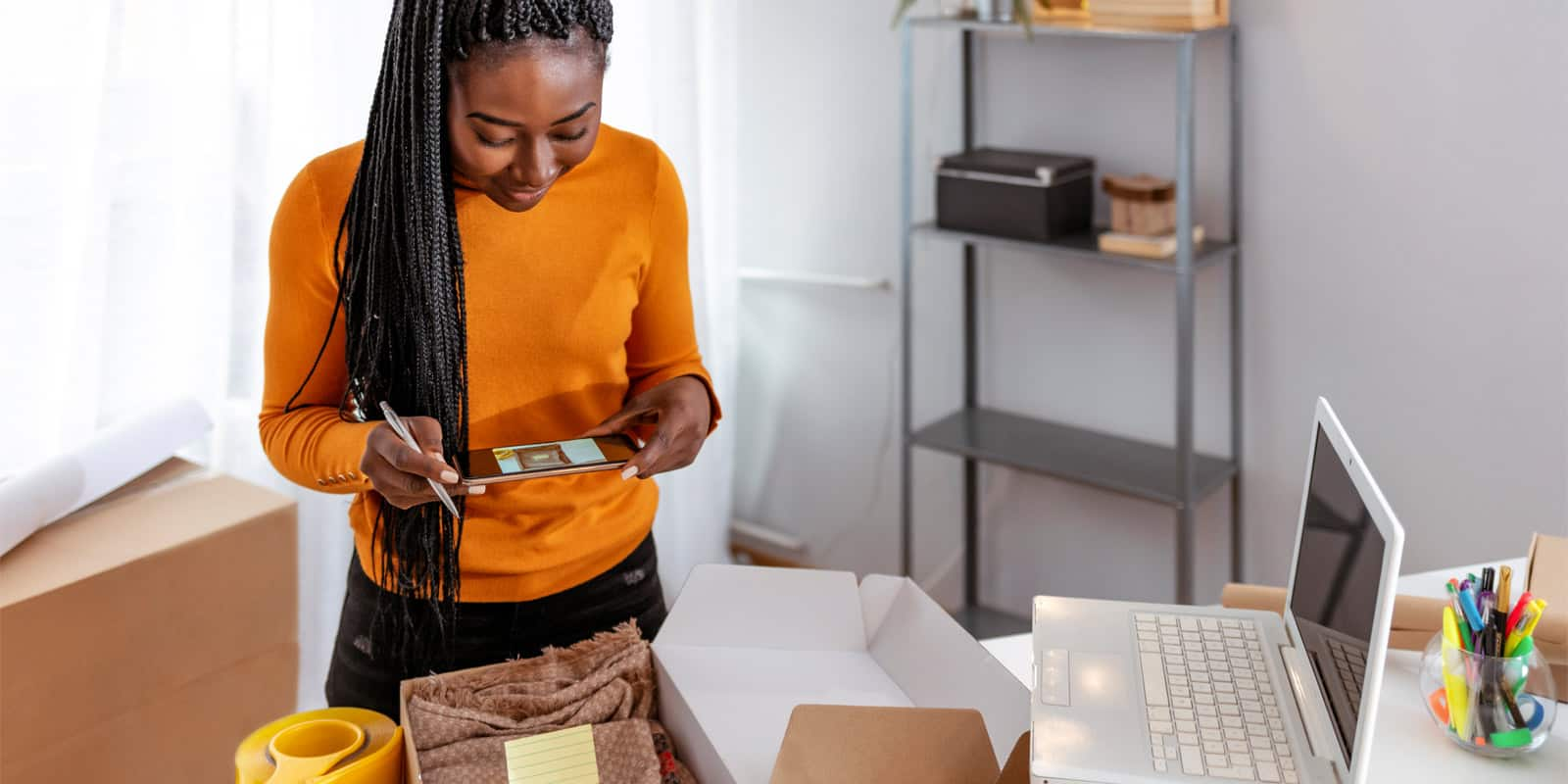 Female business owner taking photo of shipping box content
