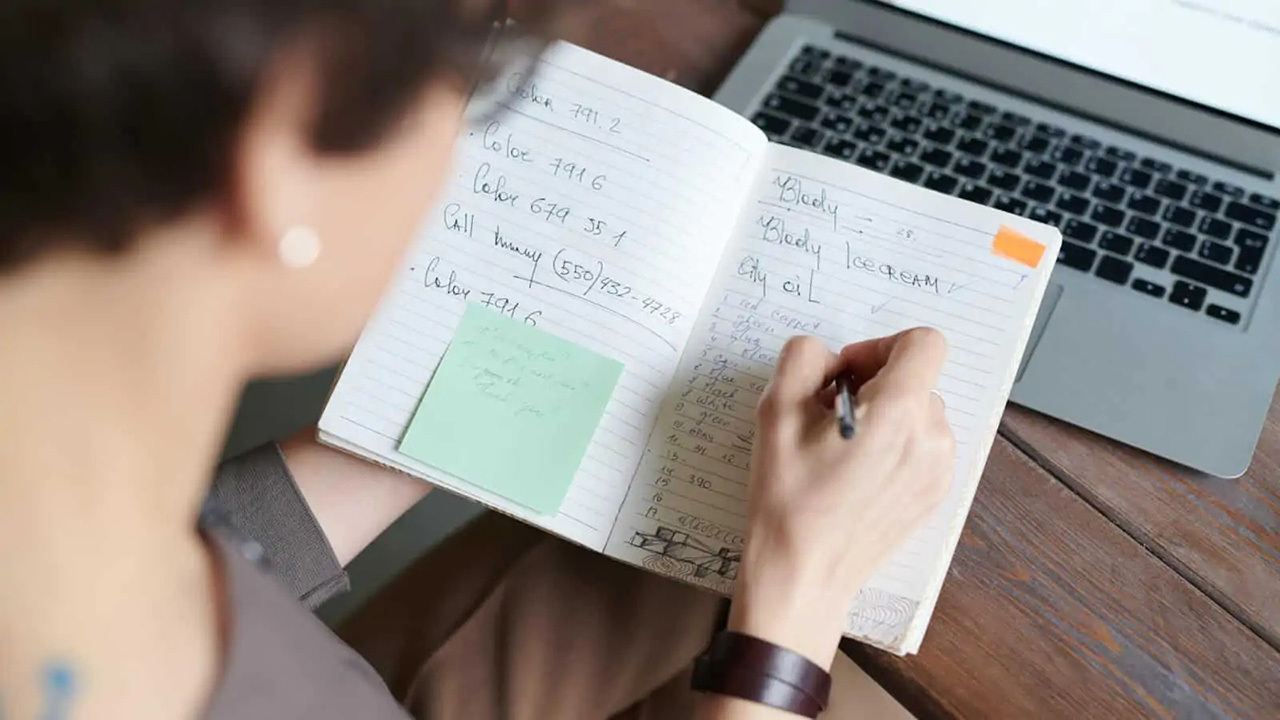 An individual plans a business in a notebook