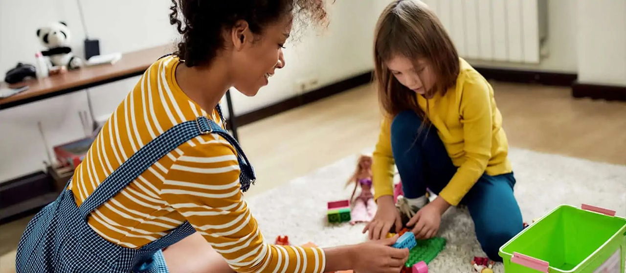A female babysitter plays with a young girl using lego blocks