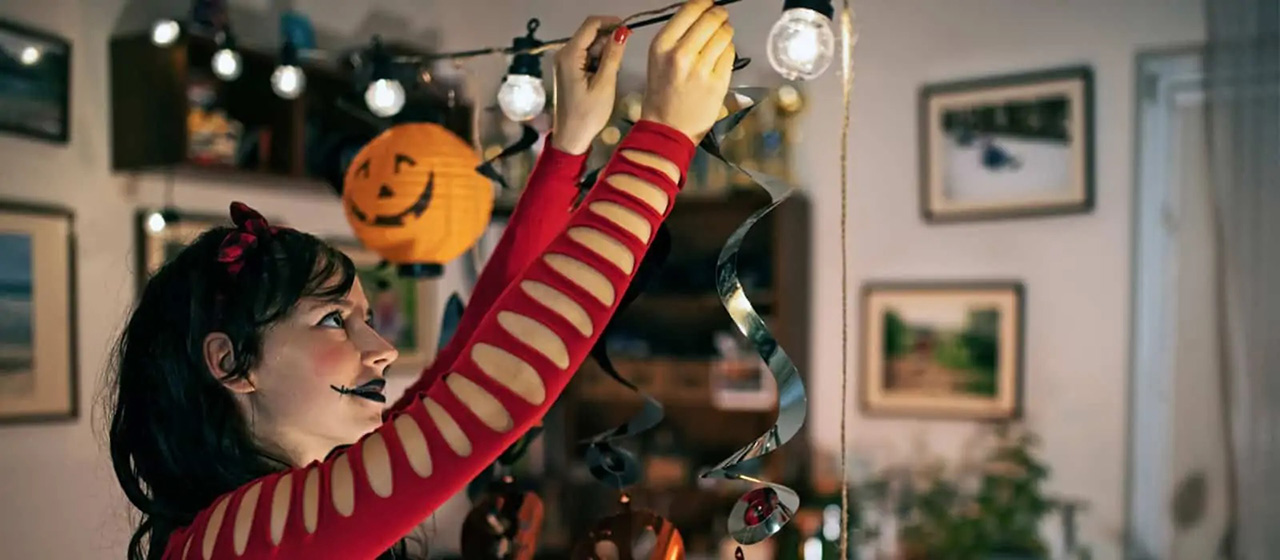 Female in a red costume hanging halloween decoration lights