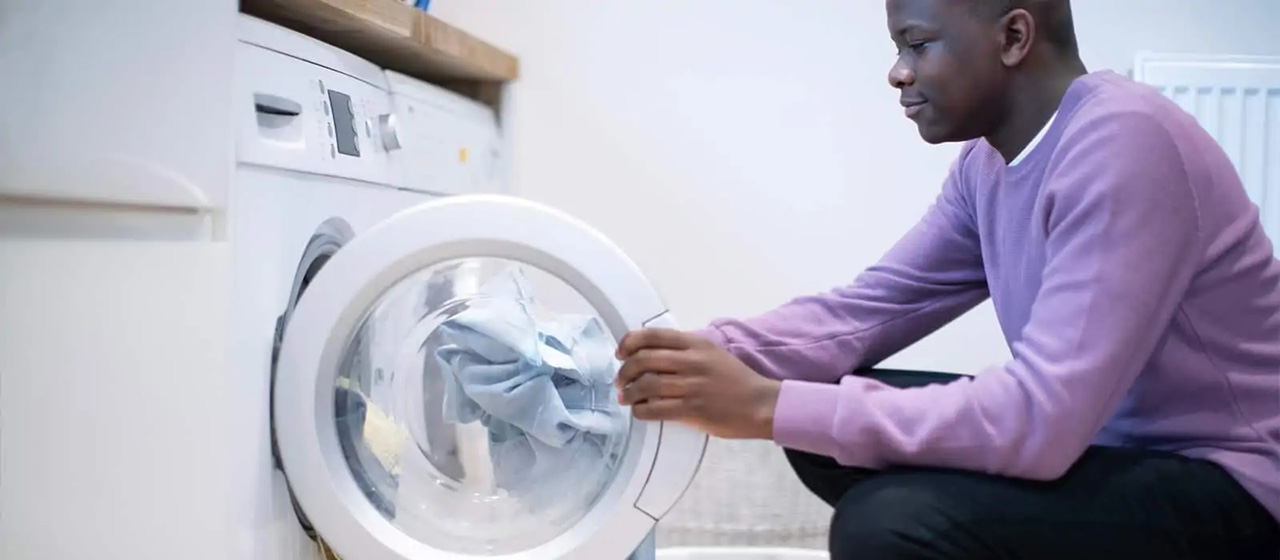 Male in purple shirt looking inside washer with laundry