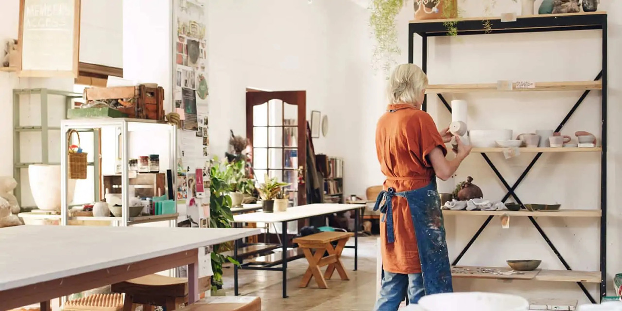 Woman in her own pottery shop wearing an apron