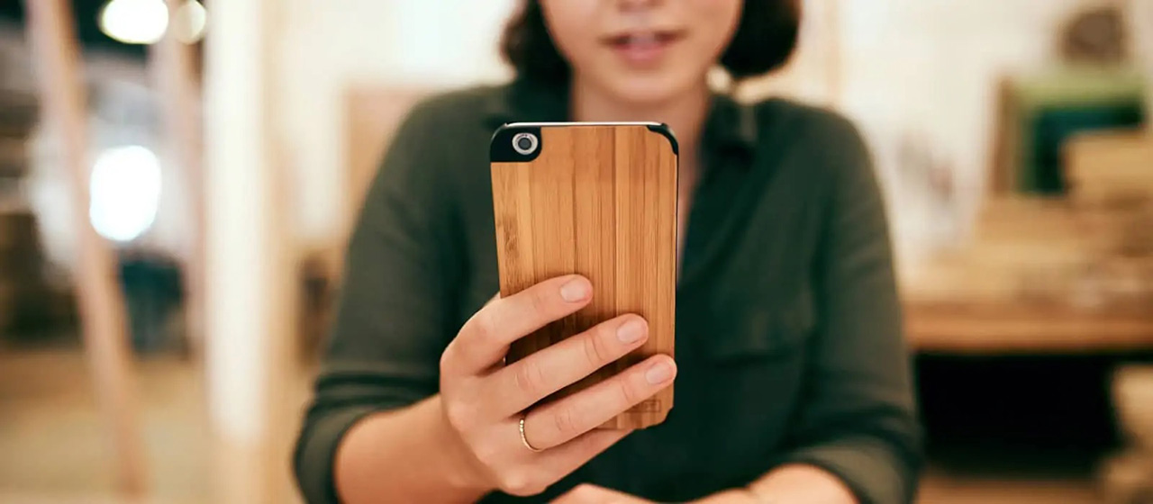 Woman holds wooden phone case