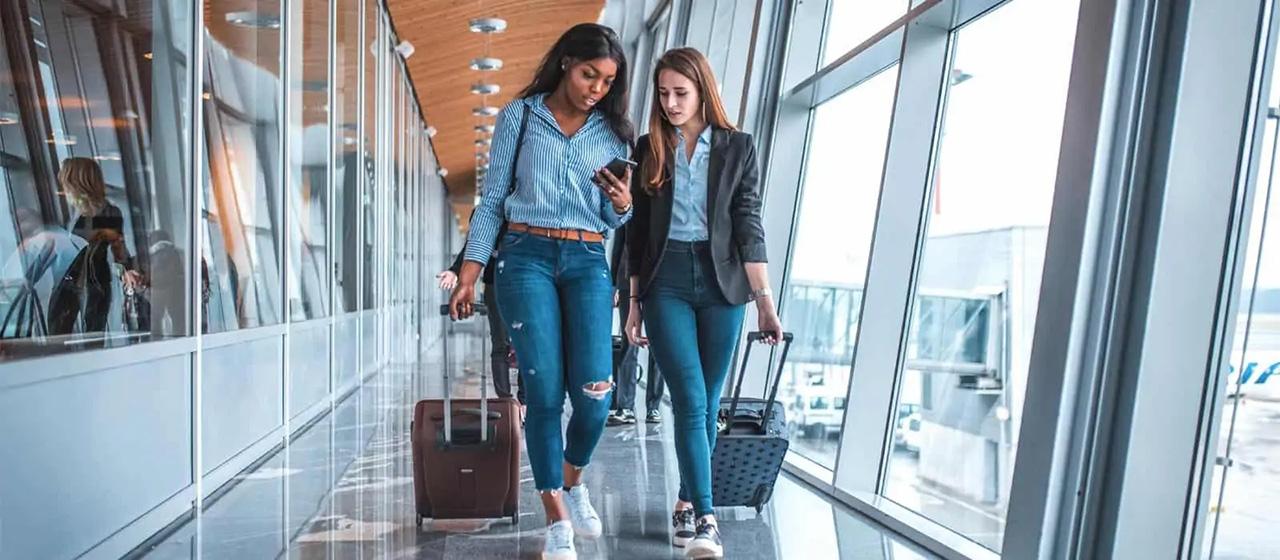 2 women walking in airport hallway
